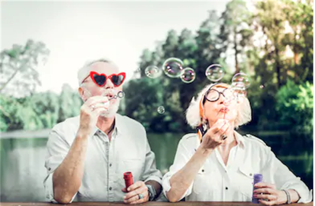 Image of two people wearing sunglasses and blowing soap bubbles.